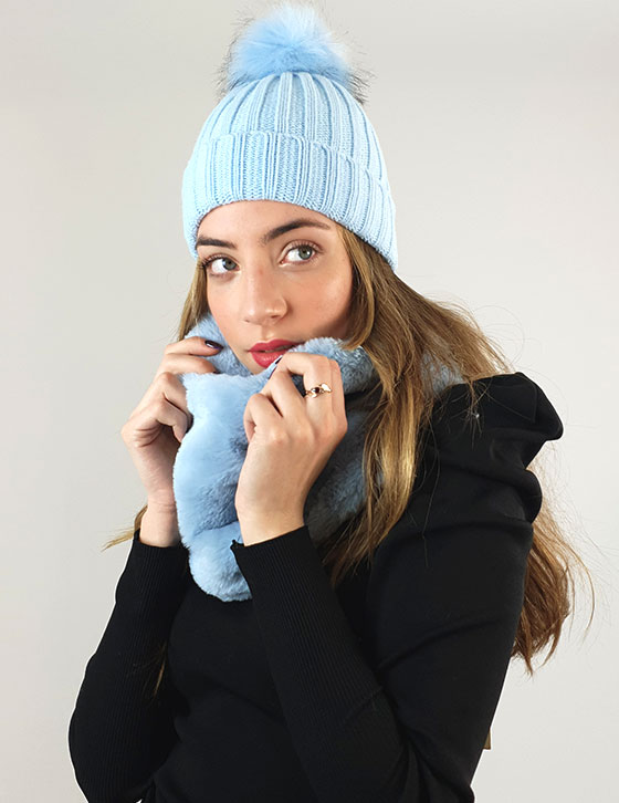 A young girl wearing a hat talking on a cell phone